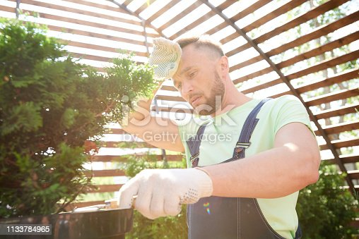Low angle portrait of exhausted gardener planting trees in extreme heat and sunlight, copy space