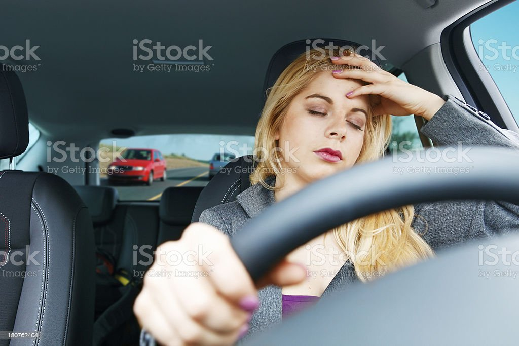 Tired girl driving a car stock photo