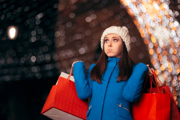 tired girl holding shopping bags on christmas lights décor - holiday foto e immagini stock