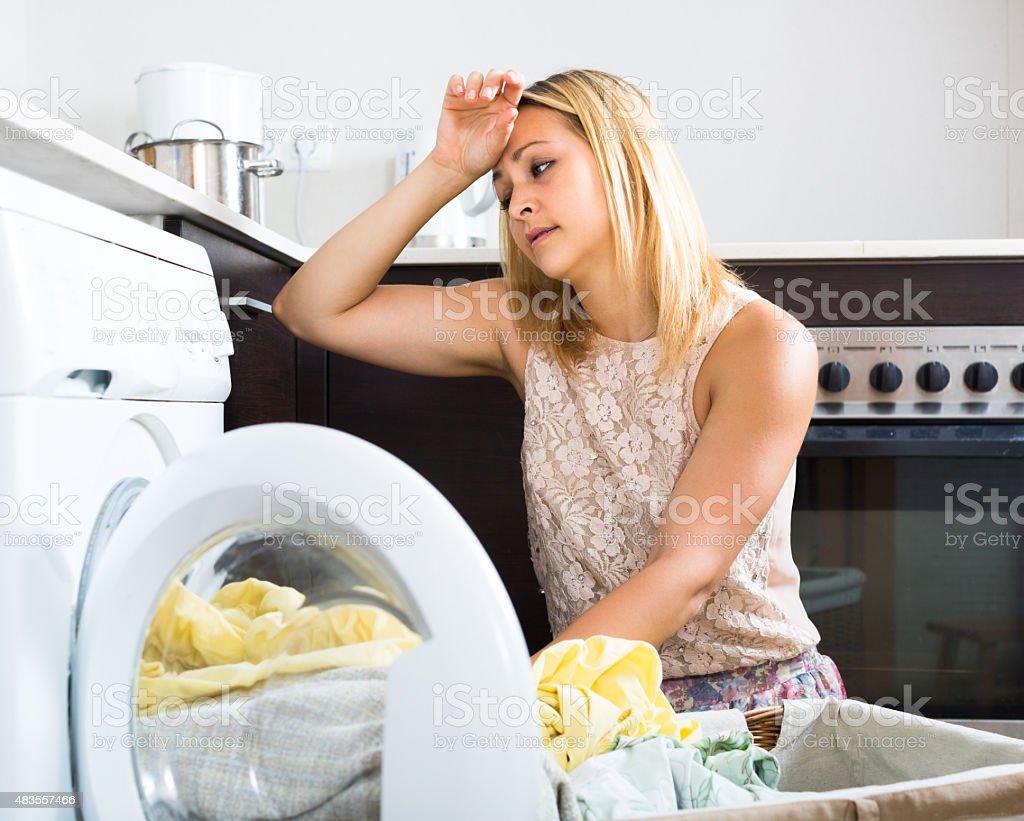 Tired girl near washing machine stock photo
