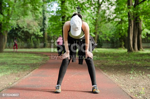 istock Tired girl on the run track stands bent and looking down 672040602