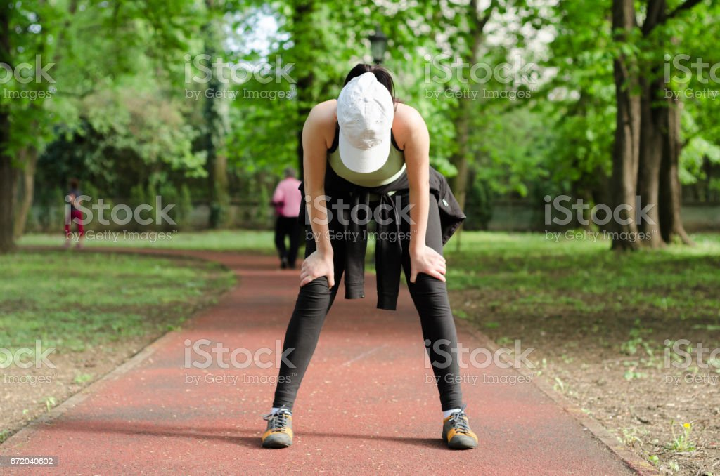 Tired girl on the run track stands bent and looking down - foto de acervo