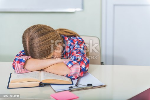 Exhausted female teenager is sitting near polished desk. She falling asleep on open book