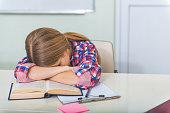 istock Tired girl sleeping in classroom 639186128