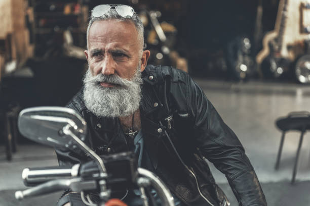 tired glance of old man on bike - biker stock photos and pictures