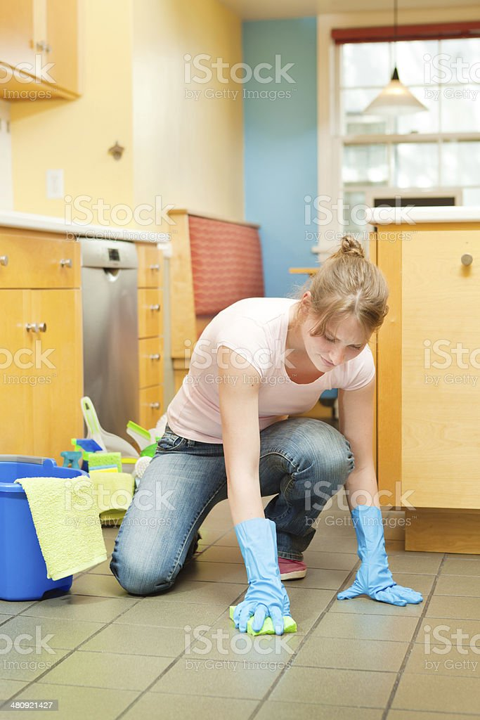 Tired Housewife Cleaning Floor of Kitchen stock photo