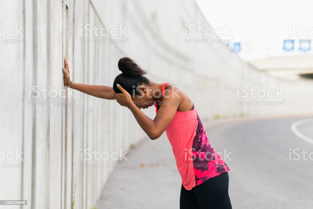 Tired jogger Young woman leaning on the concrete wall, taking a break Adult Stock Photo