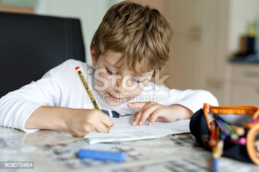 istock Tired kid boy at home making homework writing letters with colorful pens 909070454
