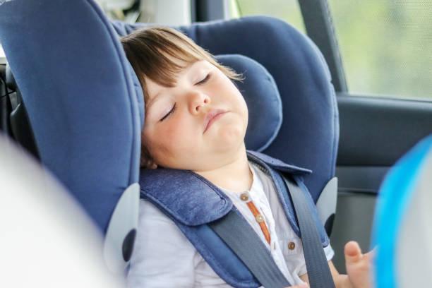 petit garçon fatigué de chéri dormant dans le siège d'auto voyageant avec des parents. transport d'enfants dans la chaise de sécurité. - child car sleep photos et images de collection