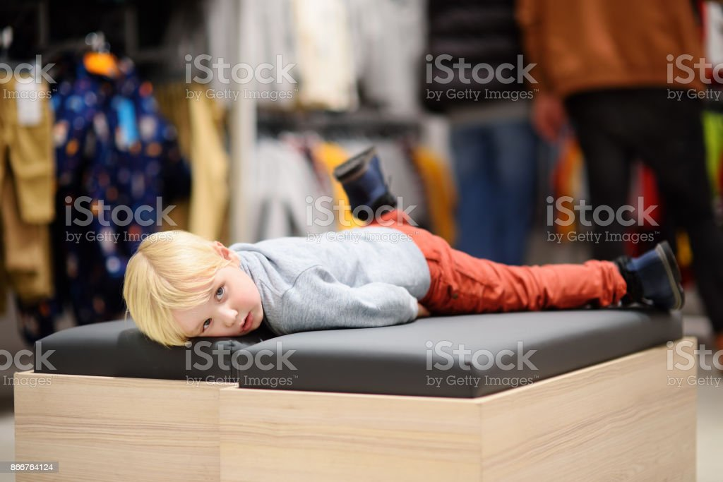 Tired little boy during shopping with parents stock photo