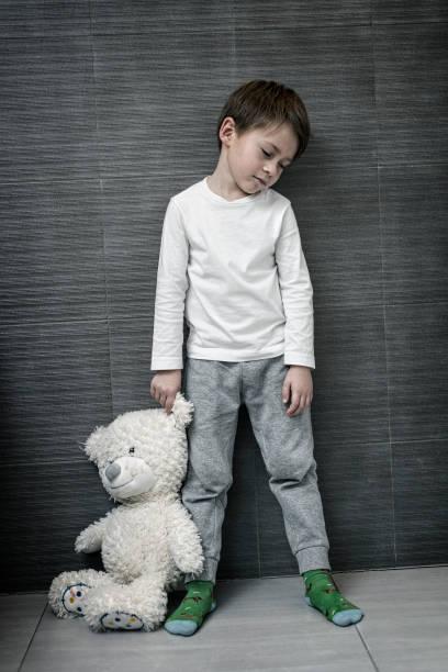 Müde kleiner Junge hält Teddybär am Ohr – Foto