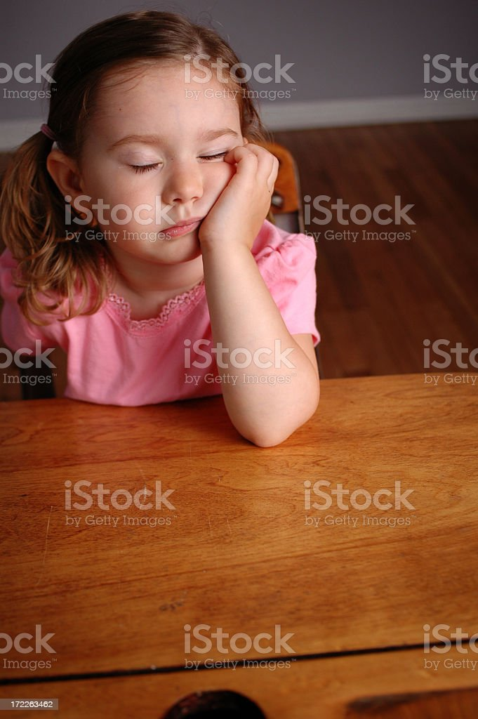 Tired Little Girl Falling Asleep in a School Desk royalty-free stock photo
