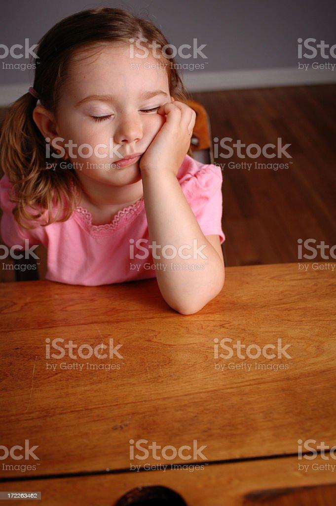 Tired Little Girl Falling Asleep in a School Desk stock photo