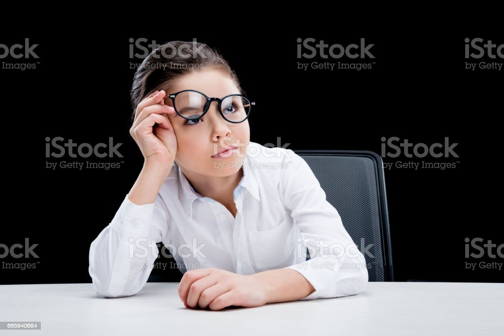 Tired little girl in formal wear sitting at table foto stock royalty-free
