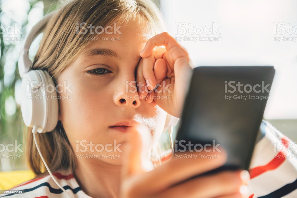 Tired Little girl with headphones using smart phone stock photo