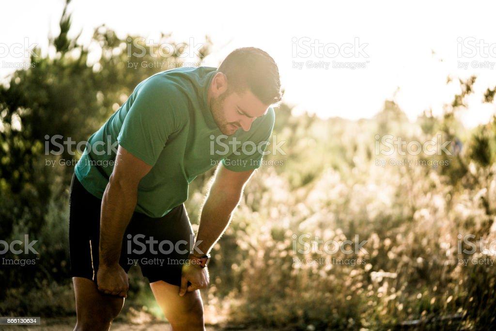 Müden männlichen Läufer biegen im Wald – Foto