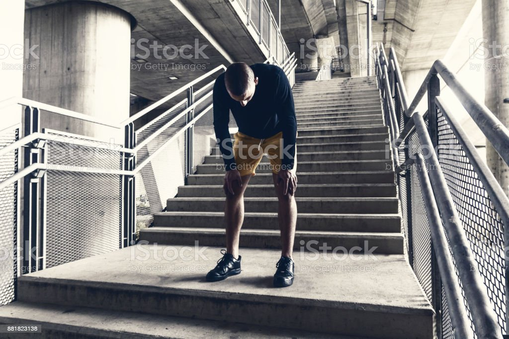 Tired male runner resting after training. stock photo