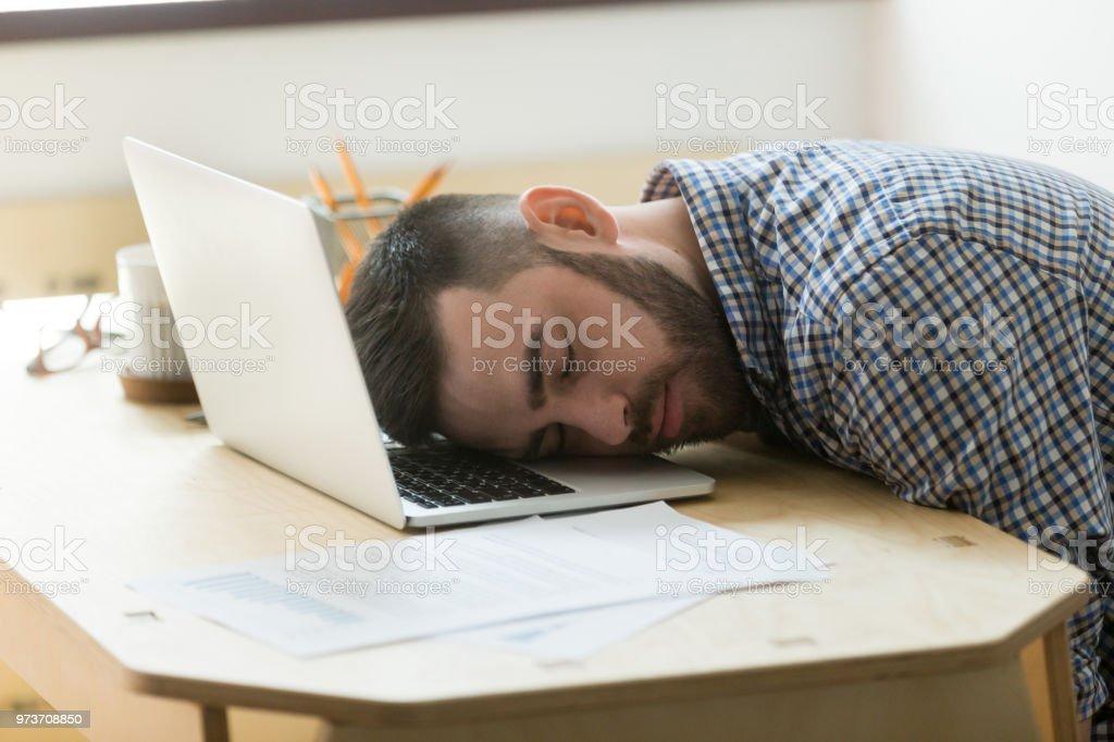 Fatigué de travailleur masculin dormir à ordinateur portable au