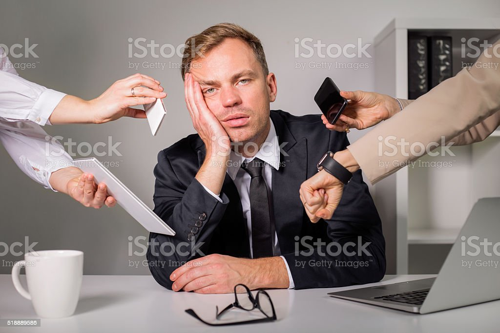 Tired man being overloaded at work stock photo