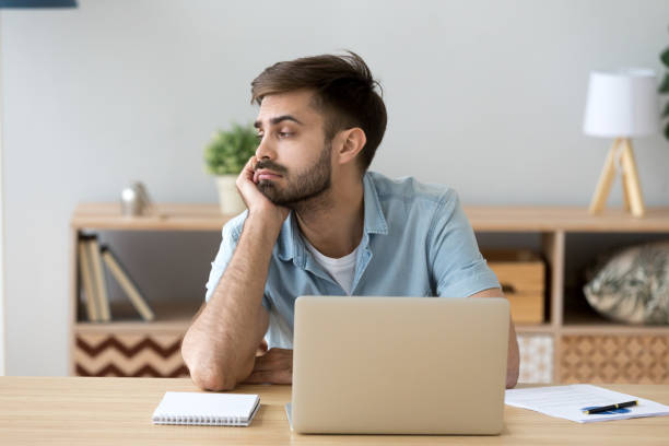 tired man distracted from computer work lacking motivation - detraction stock pictures, royalty-free photos & images