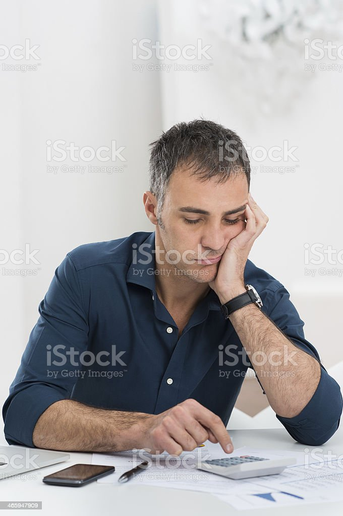Tired Man Doing Calculations stock photo