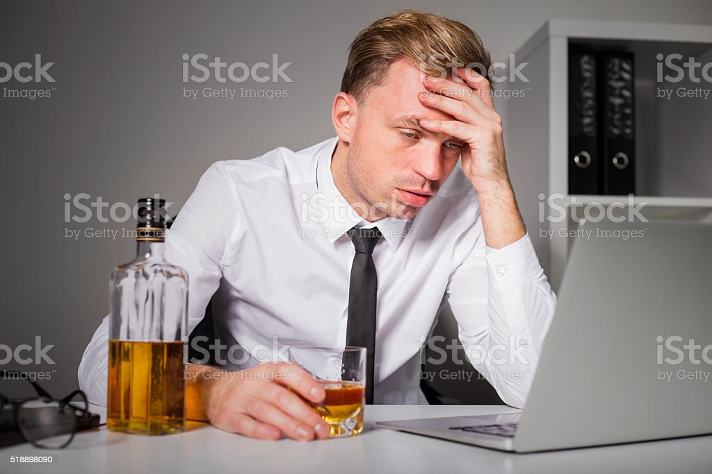 Tired man drinking at the office stock photo