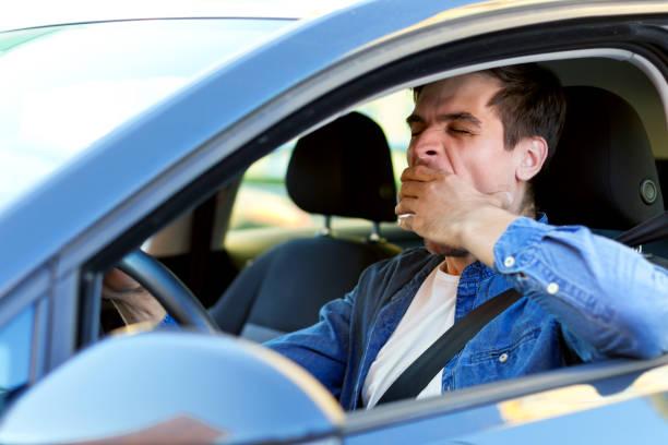 Tired man drives a car stock photo