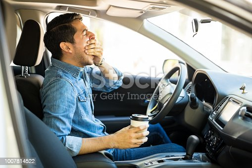 Young man feeling tired and yawning while driving a car
