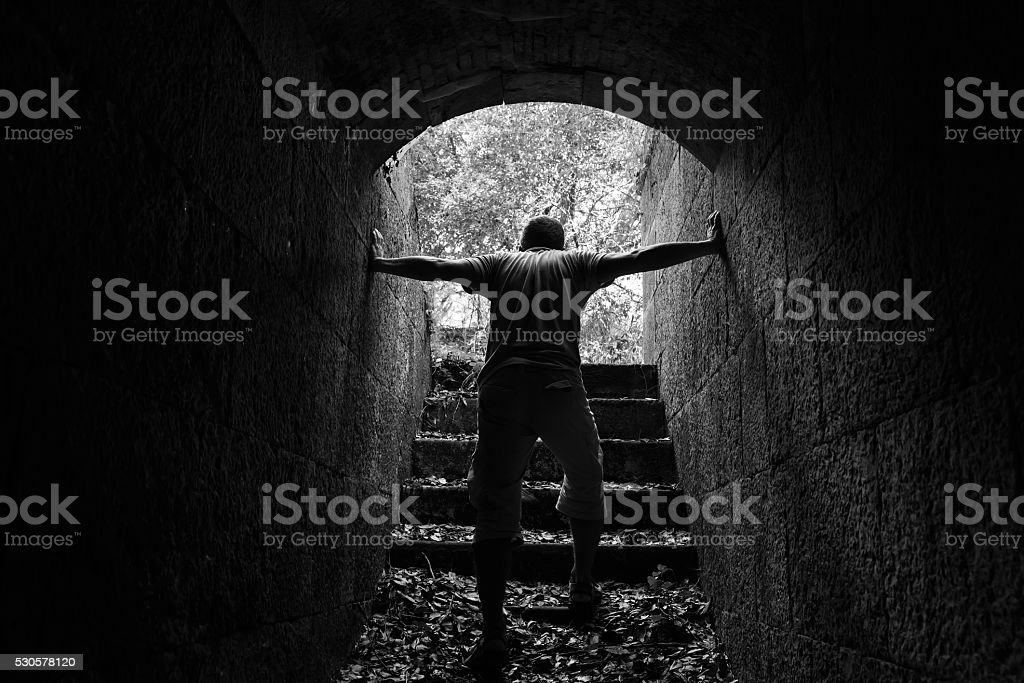 Tired man goes out of dark stone tunnel stock photo