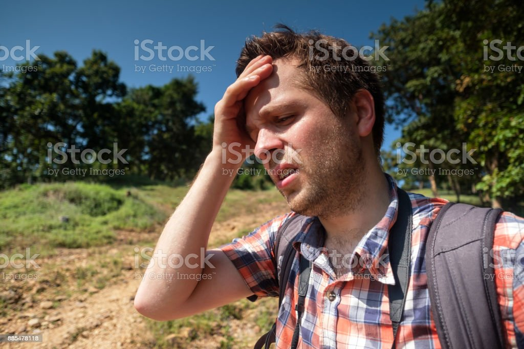 Tired Man in forest unfder strong sun with backpack. Travel in Asia alone. Suffer form sunstroke stock photo