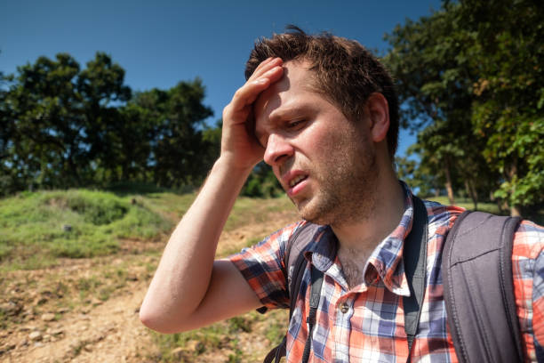 疲倦的人在森林 unfder 強的太陽與背包。獨自在亞洲旅行。遭受中暑 - 口渴 個照片及圖片檔