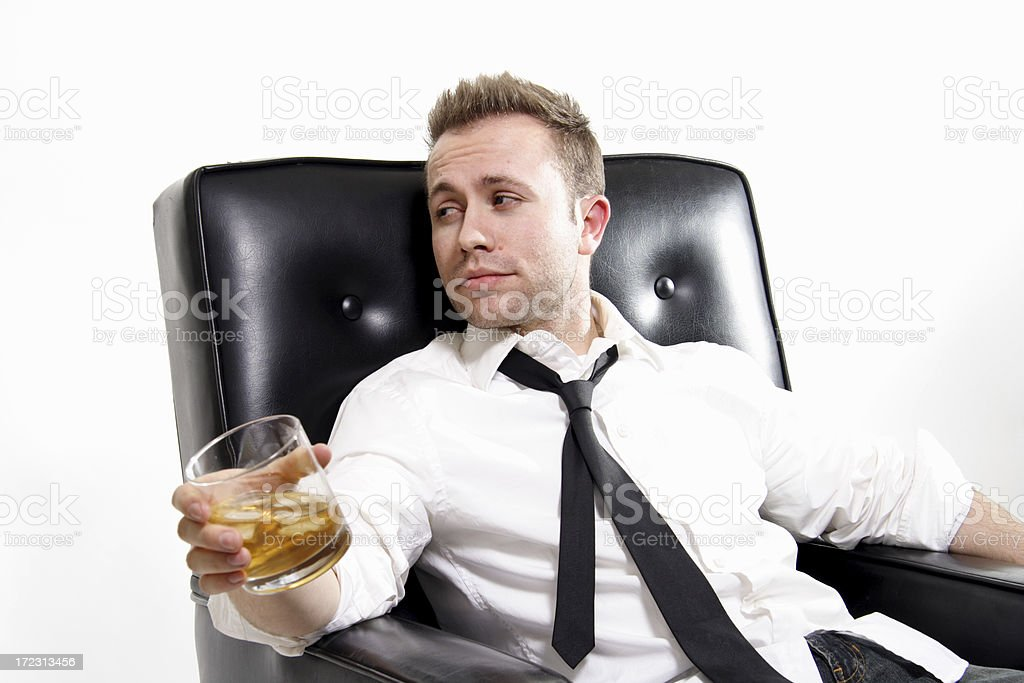 tired man in leather chair with drink royalty-free stock photo