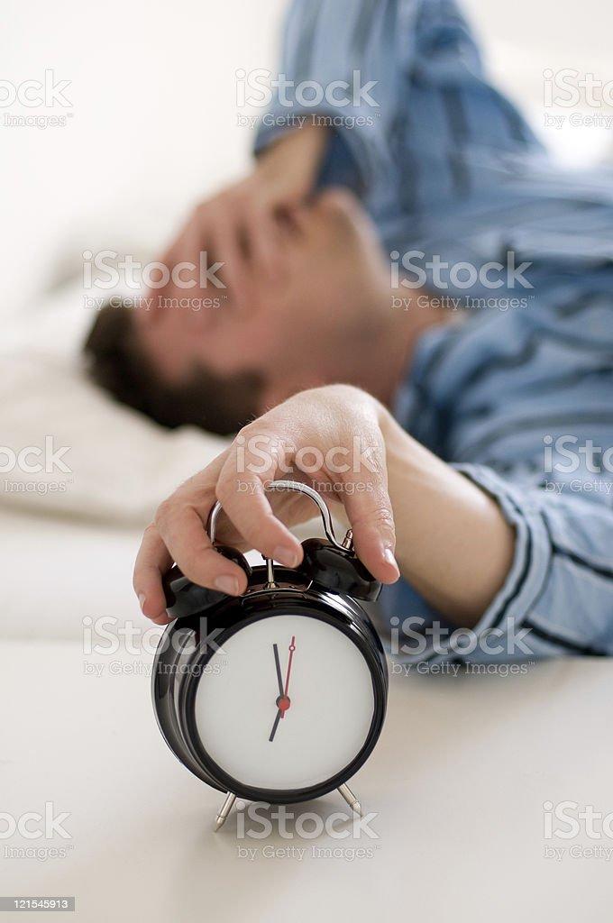 Homem cansado de pijama paradas despertador de toque - foto de acervo