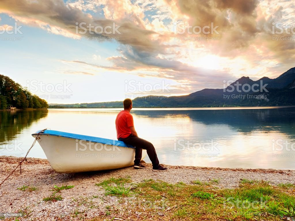 Tired man in red shirt sit, fishing boat,  mountain lake photo libre de droits