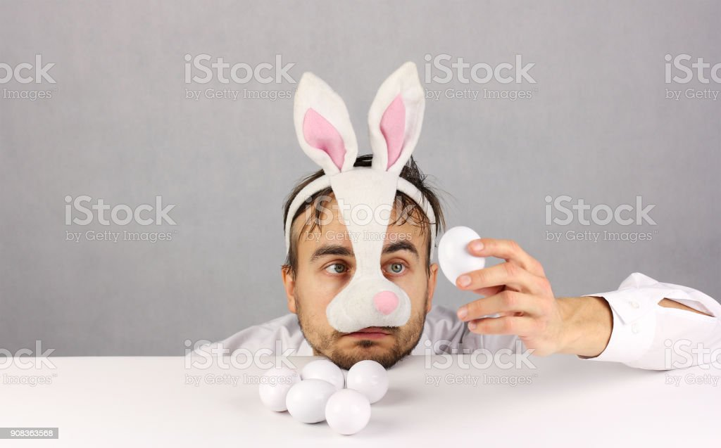 tired man in the mask Easter Bunny looking at the egg stock photo