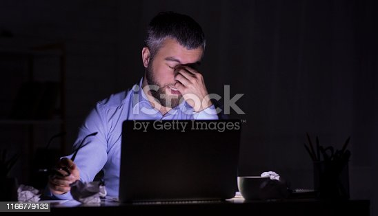 Exhausted Middle Aged Bearded Businessmen Is Sitting In Front Of Laptop In Dark Room, overworking, copy space