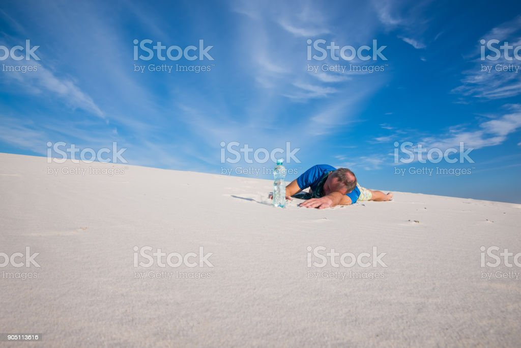 Tired man lies in the sand next to a bottle of water stock photo