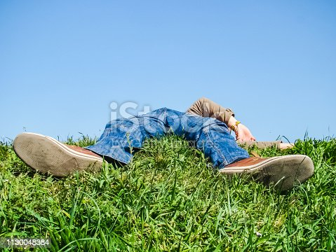tired man lying on the grass is resting tired man lying on the grass is resting
