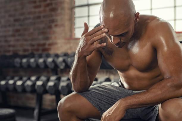 müder mann ruht nach starkem training - mit muskelkater trainieren stock-fotos und bilder