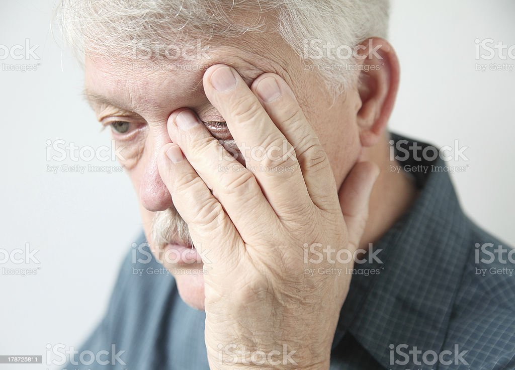 tired man rubbing his eye stock photo