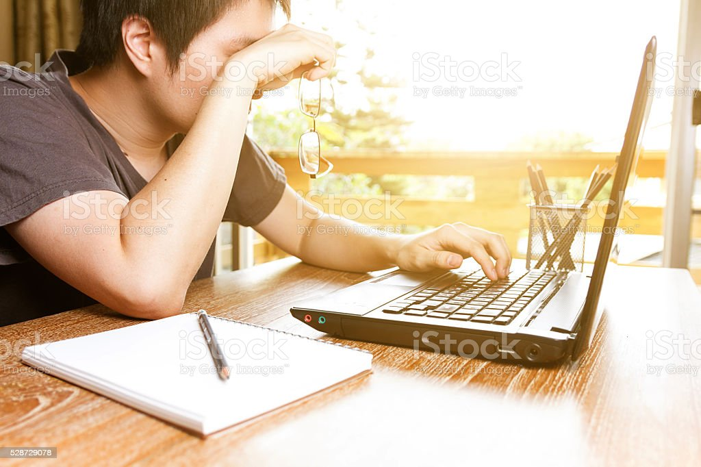 tired man rubbing his eyes while using laptop computer stock photo
