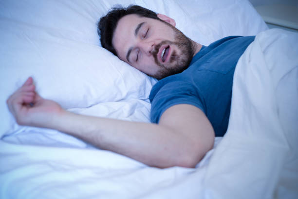 Tired man sleeping and snoring loudly in the bed stock photo