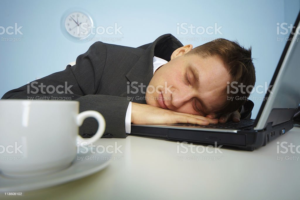 Tired man sleeping on a notebook royalty-free stock photo