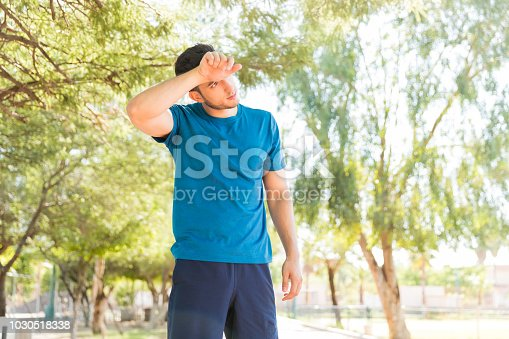 Tired young man wiping his forehead after jogging in park on sunny day