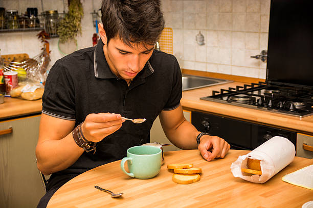 müder mann mit kaffee sitzen im kitchen table - migräne vorbeugen stock-fotos und bilder
