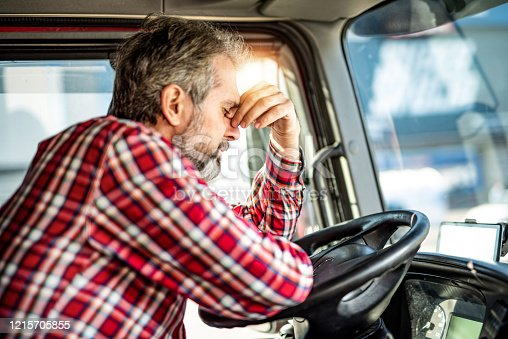 1001622522 istock photo Tired mature truck driver waiting in traffic and contemplating about job problems. 1215705855