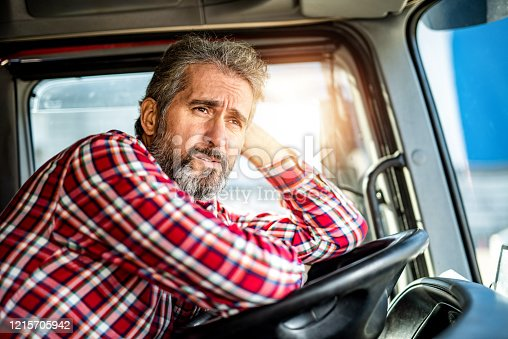 1001622522 istock photo Tired mature truck driver waiting in traffic and contemplating about job problems. 1215705942