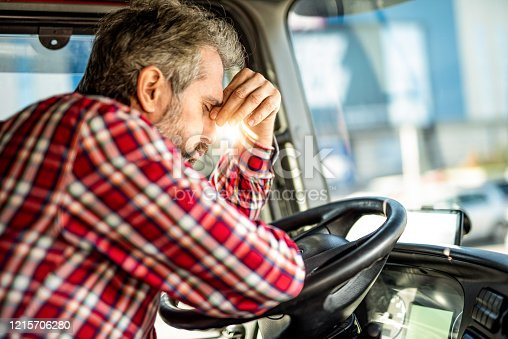 Distraught truck driver leaning on a steering wheel and having a headache.