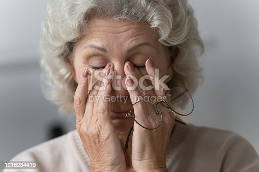 1049512672 istock photo Tired mature woman rubbing nose bridge after taking off eyewear. 1218234419