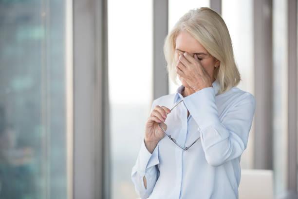 müde reife frau nehmen brille leiden unter kopfschmerzen - schwindelig stock-fotos und bilder
